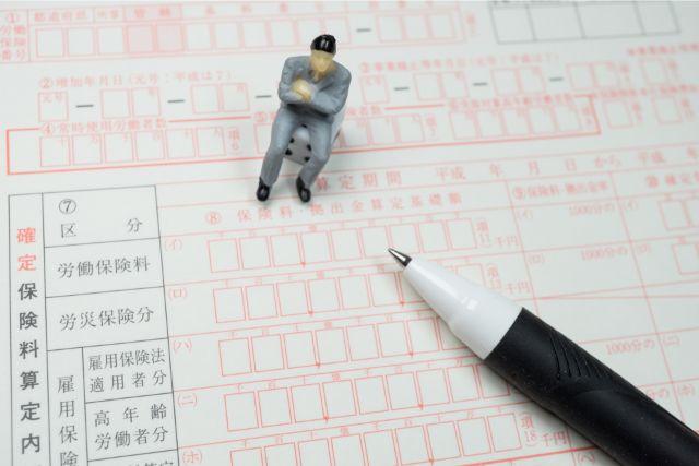 申請書類の上に置かれた人形とペン